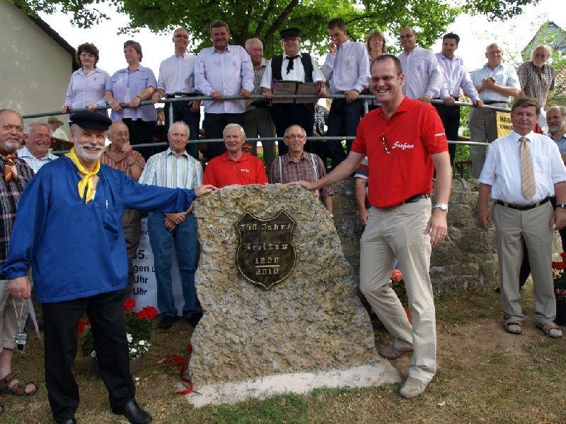 Landrat Stefan Reuss (r.) enthüllt zusammen mit Richard Kröll (l.) den Gedenkstein zur 750 Jahr-Feier